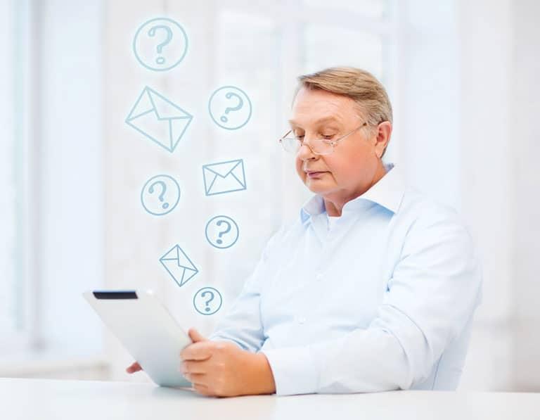 Ein älterer Mann hat ein Tablet in der Hand und einen fragenden Blick aufgesetzt.