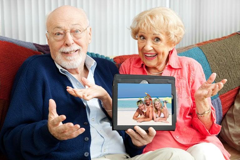 Ein glückliches Senioren-Pärchen präsentiert stolz ein Tablet auf dem ein Familienfoto am Strand zu sehen ist.