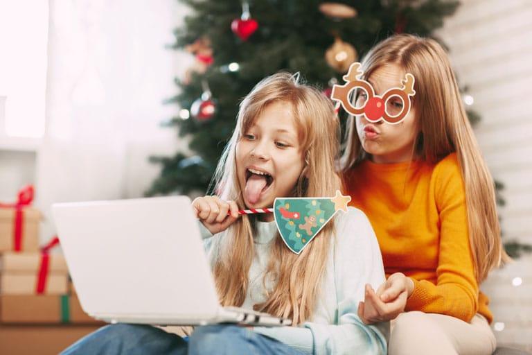 Zwei junge Mädchen sitzen vor dem Laptop und haben einen Videoanruf mit Verwandten.