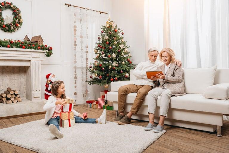 Zwei Senioren sitzen mit Tablet auf der Couch vor einem geschmückten Christbaum. Die Enkeltochter sitzt davor am Boden und packt ihre Geschenke aus.