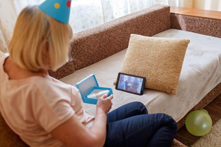 Eine ältere Dame sitzt mit einem Tablet auf der Couch und hat eine Videokonferenz mit ihrer Familie geöffnet. Dazu packt sie ein kleines verpacktes Geschenk aus.