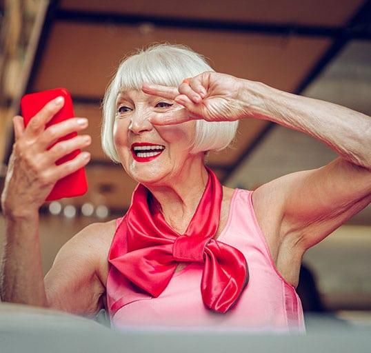 Eine ältere Dame macht ein Videoanruf mit ihrem Telefonat und ist glücklich dabei.