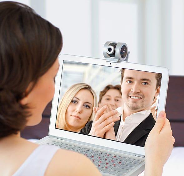 Eine Frau führt ein Videotelefonat mit jungen Leuten über ihrem Laptop. Dazu hat sie eine Webcam auf dem Laptop befestigt.